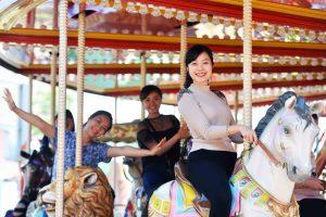 Royal Carousel, Đu Quay Kỳ Diệu, người phụ nữ mặc áo xám đang dơ tay, mô hình ngựa màu trắng, ảnh chụp ban ngày