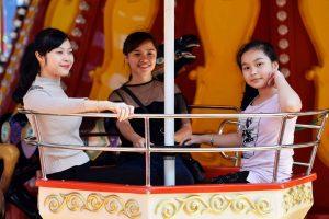 Royal Carousel, Đu Quay Kỳ Diệu, 3 người đang ngồi trên mô hình đu quay, ảnh chụp ban ngày