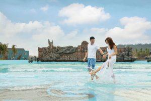 Hình ảnh chụp cặp đôi đi dạo khu trò chơi sóng thần, ảnh chụp ngoài trời, bầu trời nhiều mây, chàng trai áo phông polo trắng nắm tay cô gái váy trắng đang đi trên mặt nước, cây cối xanh tươi, quang cảnh khu vui chơi sóng thần
