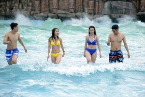 4 du khách đang đứng mỉm cười tại trò chơi Sóng thần, ảnh chụp ở khu trò chơi sóng thần,
