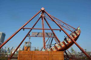 Tàu Hải Tặc, mô hình tàu sơn màu nâu, nhiều người đang ngồi trên mô hình tàu, trời nắng, trời xanh, ảnh chụp ban ngày