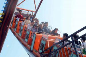 Tàu Hải Tặc, nhiều người đang ngồi trên hàng ghế màu cam, trời nắng, ảnh chụp ban ngày