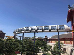 Tàu Monorail, đoàn tàu màu trắng nhiều khoang, nhiều cây xanh bên dưới, trời xanh, trời nắng, ảnh chụp ban ngày