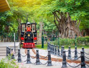 Tàu Thám Hiểm Halong Railway, mô hình tàu hỏa màu xanh, đường sắt màu nâu, nhiều cây xanh phía xa, bậc thang màu xám, ảnh chụp ban ngày