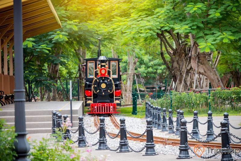 Tàu Thám Hiểm Halong Railway, mô hình tàu hỏa màu xanh, đường sắt màu nâu, nhiều cây xanh phía xa, bậc thang màu xám, ảnh chụp ban ngàyTàu Thám Hiểm Halong Railway, mô hình tàu hỏa màu xanh, đường sắt màu nâu, nhiều cây xanh phía xa, bậc thang màu xám, ảnh chụp ban ngày