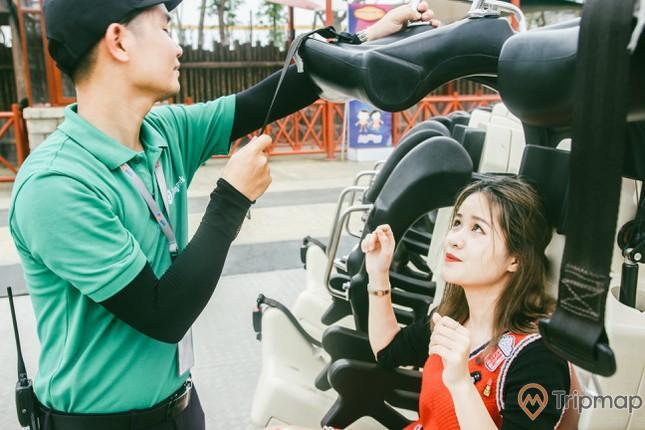 nhân viên áo xanh lá đeo bảo hộ cho du khách nữ trước khi chơi trò Tê Giác Cuồng Nộ