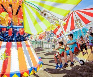 Thằn Lằn Bay, nhiều người đang trải nghiệm trò chơi, cậu bé mặc áo xanh đang trải nghiệm, nền đường màu xám, trời nắng, ảnh chụp ban ngày