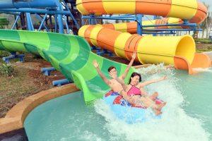 Du khách trải nghiệm trò chơi Thử thách mãng xà, 2 người ngồi trên phao trượt xuống bể nước, ảnh chụp ngoài trời, máng trượt màu và và màu xanh lá