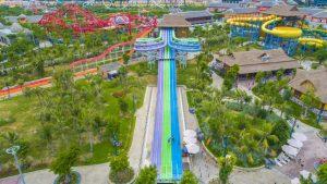 Toàn cảnh trò chơi Tia chớp khổng lồ, ảnh chụp từ trên cao, cây cối tỏng khuôn viên khu vui chơi xanh tươi, những máng trượt màu sắc
