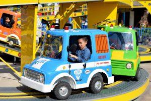 Tour de Paris, mô hình xe hơi màu xanh, em bé mặc áo xanh ngồi trong xe hơi màu xanh, trời nắng, ảnh chụp ban ngày