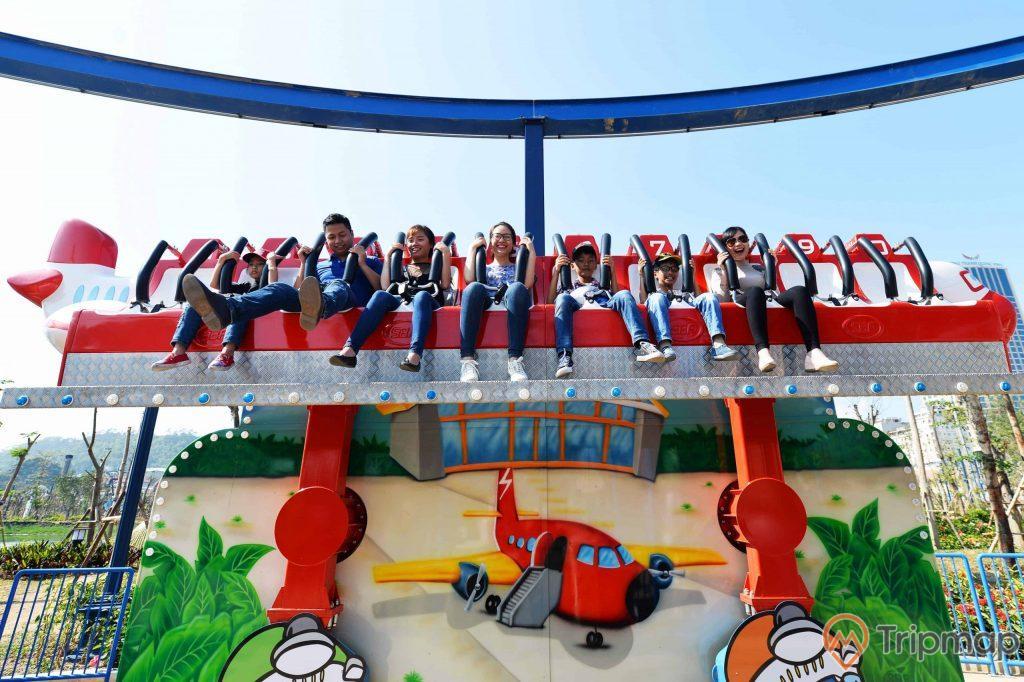 Vũ Công Thực Thụ, nhiều người đang trải nghiệm trò chơi, nhiều người đang ngồi trên ghế màu đỏ, hình vẽ máy bay màu đỏ, trời nắng, ảnh chụp ban ngày