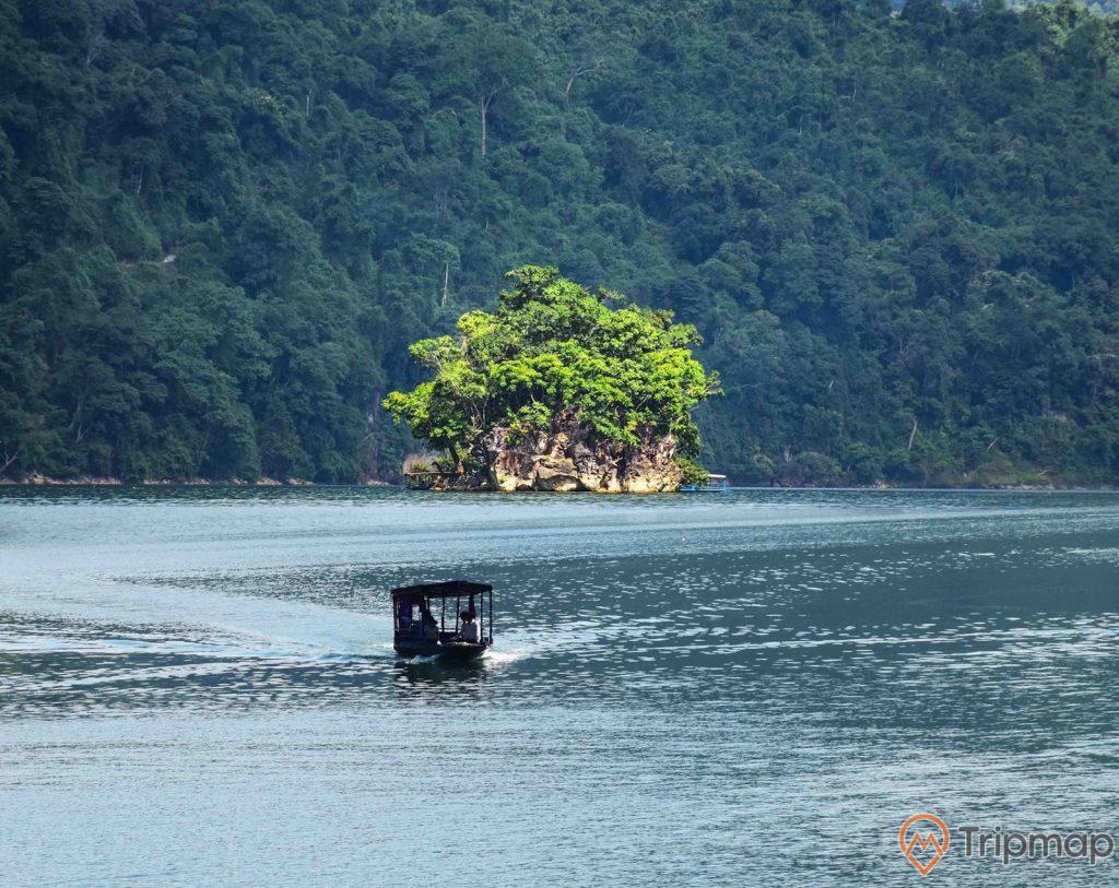 Đảo Bà Goá phía xa, chiếc thuyền đang đi trên mặt hồ, ảnh chụp ngoài trời