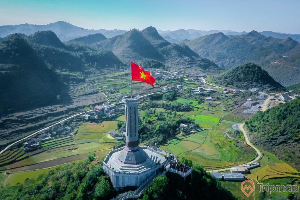 Cột cờ Lũng Cú thuộc xã Lũng Cú, huyện Đồng Văn, ảnh chụp từ trên cao, đồi núi phía xa xa, cây cối xanh tươi