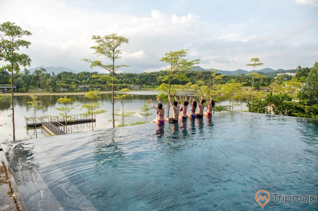 du khách đang ngồi trên thành bể bơi ngoài trời, cây cối xanh tươi, bầu trời nhiều mây trắng