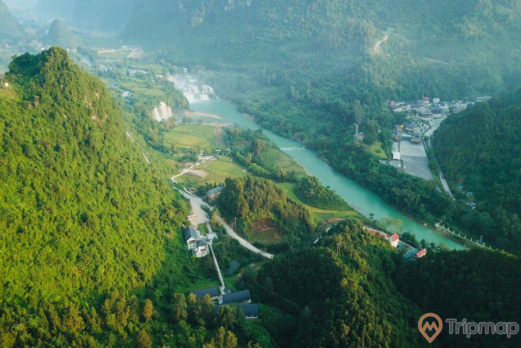 toàn cảnh Khu nghỉ dưỡng Sài Gòn – Bản Giốc 4 sao, cây cối xanh tươi, dòng sông