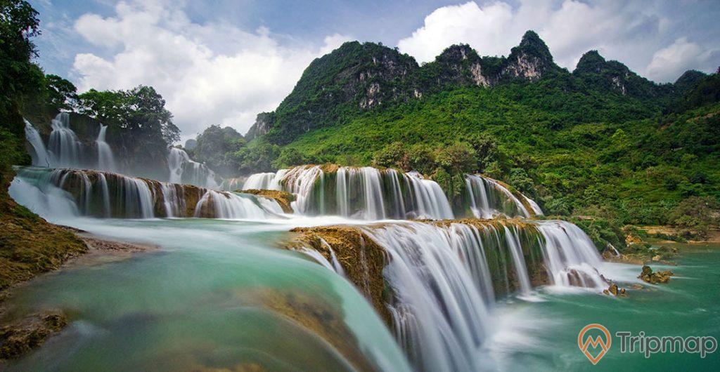 thác bản giốc đang chảy, cây cối xanh tươi, bầu trời nhiều mây trắng, ảnh chụp ngoài trời gần thác nước