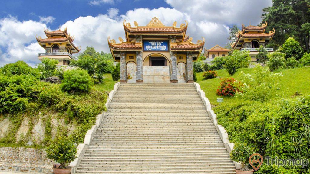 Cổng tam quan thiền viện trúc lâm tây thiên, bầu trời nhiều mây trắng, cây cối xanh tươi hai bên bờ bậc thang