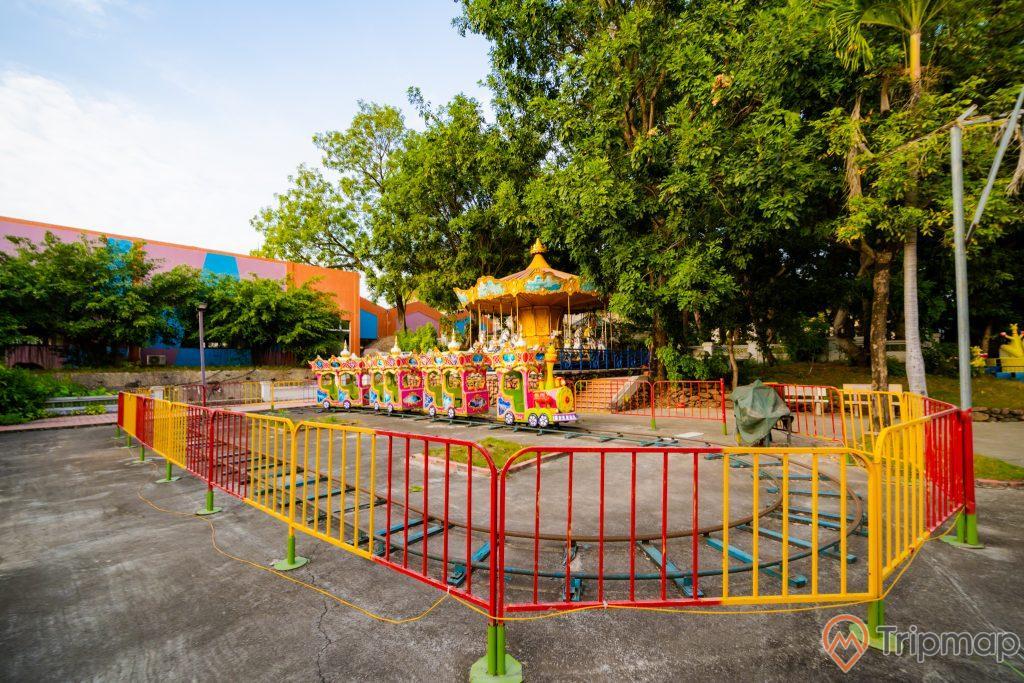 Tuần Châu Park, mô hình tàu hỏa, hàng rào sơn màu vàng và đỏ, đường ray màu xanh, nền đường màu xám, nhiều cây xanh, ảnh chụp ban ngày