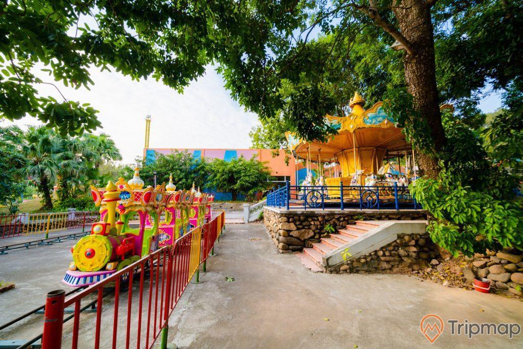 Tuần Châu Park, mô hình tàu hỏa, nền đường màu xám, bậc thang màu đỏ, hàng rào sơn màu đỏ, nhiều cây xanh, ảnh chụp ban ngày