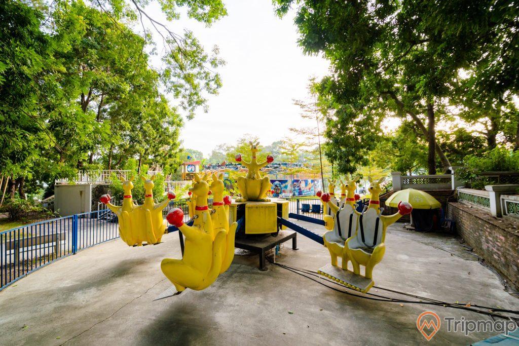 Tuần Châu Park, trò chơi trẻ em, mô hình con huơu màu vàng, nền đường màu xám, hàng rào màu xanh, nhiều cây xanh, ảnh chụp ban ngày