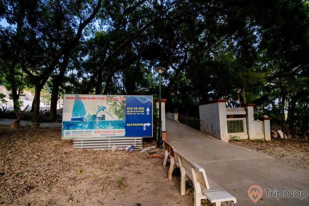 Tuần Châu Park, bảng chỉ đường màu xanh, ghế đá màu trắng, nền đường màu xám, nền đất màu nâu, nhiều cây xanh, ảnh chụp ban ngày