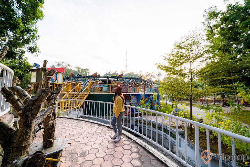 Tuần Châu Park, nền gạch màu đỏ hình tổ ong, thân cây gỗ, cô gái mặc áo vàng đang đứng trên nền gạch đỏ, nhiều cây xanh, ảnh chụp ban ngày