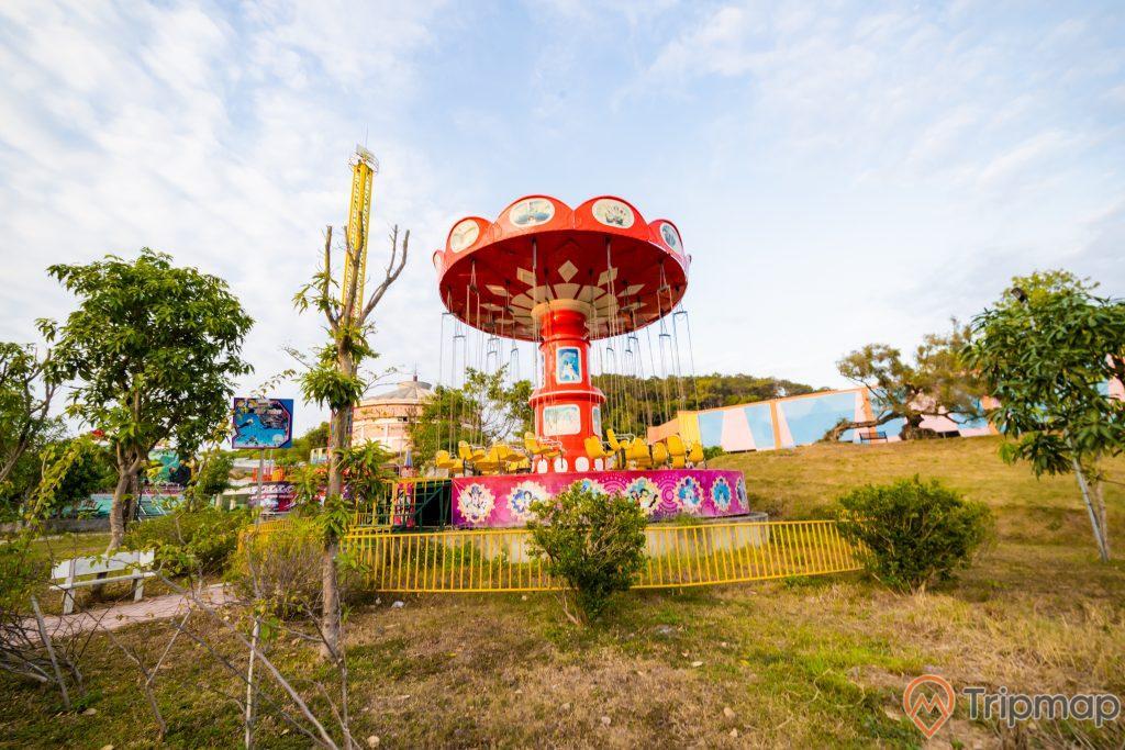 Tuần Châu Park, nền đất màu nâu có cây xanh, nhiều cây xanh, trụ quay màu đỏ, trời xanh nhiều mây, ảnh chụp ban ngày