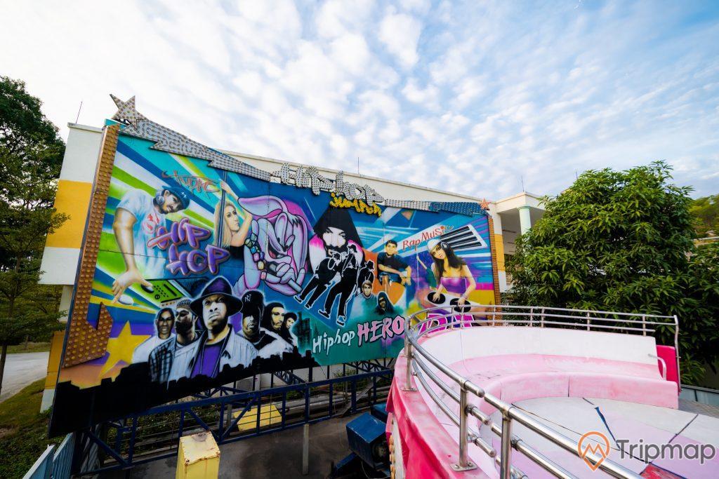 Tuần Châu Park, trò hiphop jumper, biển quảng cáo nhiều hình người, ghế ngồi màu hồng, nhiều cây xanh, trời xanh nhiều mây, ảnh chụp ban ngày