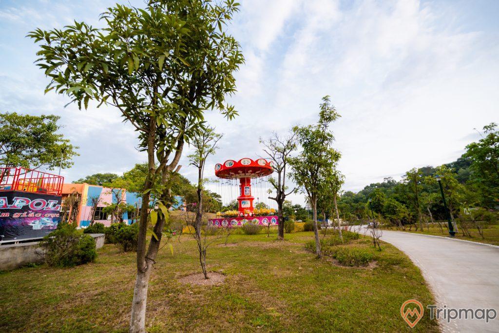 Tuần Châu Park, nhiều cây xanh, nền đường màu xám, thảm cỏ xanh, trụ quay màu đỏ, trời xanh nhiều mây, ảnh chụp ban ngày